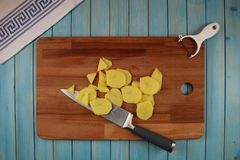 Potatoes on a wooden board for cutting vegetables stock images