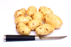 Potatos and knife. Color photograph of raw potatos Royalty Free Stock Photography