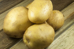 Potatos on wood place. Row potatos on wood place Royalty Free Stock Image