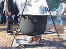Pote caliente de ebullición del hierro que cuelga sobre el fuego abierto fotografía de archivo