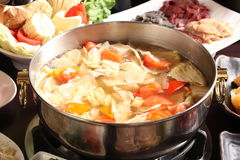 Pote caliente vegetal con maíz, col, el tomate, la carne de vaca y el cerdo en c Foto de archivo