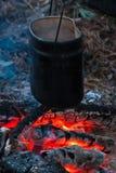 Pote colgante sobre los carbones que brillan intensamente en noche de verano foto de archivo libre de regalías