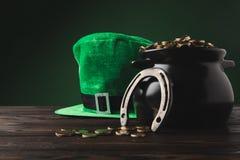 Pote con el sombrero de oro de las monedas, de herradura y verde en la tabla fotografía de archivo