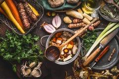 Pote con las verduras y la cuchara coloridas cortadas el cocinar en fondo rústico oscuro de la tabla con los ingredientes y el ki imagenes de archivo