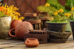 Pote de arcilla, cesta con las flores en una tabla de madera Foto de archivo
