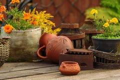 Pote de arcilla, cesta con las flores en una tabla de madera Naturmot en el viejo estilo Foto de archivo