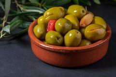 Pote de arcilla con las aceitunas del artesano preservadas en aceite de oliva virginal adicional, vinagre, especias con las pimie imagen de archivo libre de regalías