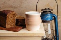 Pote de arcilla con leche, pan de centeno y la linterna de keroseno Fotografía de archivo
