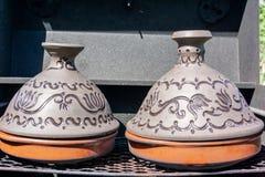 Pote de cer?mica marroqu? tradicional del tagine del tajine en un d?a de verano soleado de la parrilla negra imagen de archivo