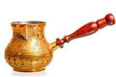 Pote de cobre amarillo del café con la manija de madera en un fondo blanco Fotografía de archivo