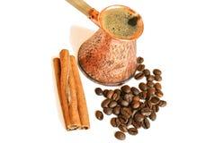 Pote de cobre del café turco del vintage (cezve o ibrik), granos de café y palillos de canela en blanco imagen de archivo