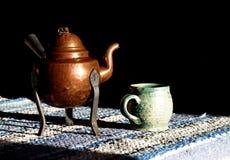 Pote de cobre viejo del café o del té y taza hecha a mano de la arcilla en la tabla de la mañana fotos de archivo libres de regalías