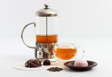 Pote de cristal del té con la taza de cristal doble de la pared echada a un lado llena de té verde con los dulces y las galletas Foto de archivo libre de regalías