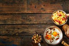 Pote de huevos revueltos y de tocino en la tabla rústica Fotos de archivo