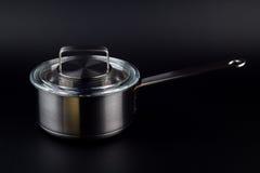 Pote de la cocina en un fondo negro Fotos de archivo