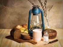 Pote de leche, de pan de centeno, de una linterna de keroseno y de verduras en la tabla Imágenes de archivo libres de regalías