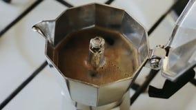 Pote de Moka que elabora cerveza en una estufa Café italiano del café express que hierve en un primer del pote del moka almacen de metraje de vídeo