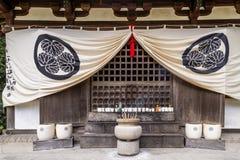 Pote de piedra con los palillos del incienso y la fila de ofrendas votivas en Chion-en el templo de Kyoto, Japón imagen de archivo libre de regalías