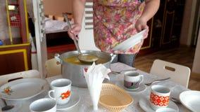 Pote de sopa y de manos con una placa vacía y una cucharón Cazo de acero del caldo, de los utensilios y de los utensilios de la c almacen de video