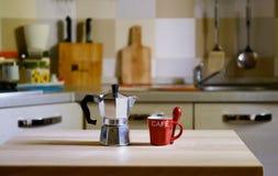 Pote del café en la tabla de madera en fondo de la cocina Fotografía de archivo