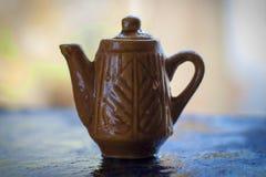 Pote del té en superficie áspera con el fondo borroso Imagen de archivo libre de regalías