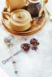 Pote del té, infuser del té del metal y taza de cerámica de té negro Composición con los accesorios del té en un fondo blanco Foto de archivo