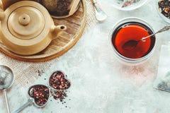 Pote del té, infuser del té del metal y taza de cerámica de té negro Composición con los accesorios del té en un fondo blanco Imagen de archivo libre de regalías