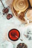 Pote del té, infuser del té del metal y taza de cerámica de té negro Composición con los accesorios del té en un fondo blanco Fotos de archivo libres de regalías