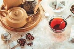 Pote del té, infuser del té del metal y taza de cerámica de té negro Composición con los accesorios del té en un fondo blanco Imágenes de archivo libres de regalías