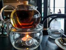 Pote del té sobre una vela con el fondo del restaurante imagenes de archivo