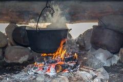 Pote en el fuego en casa del pueblo Imagen de archivo