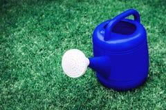 Pote plástico de riego azul en un campo de hierba verde Imagen de archivo