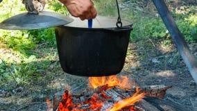Pote turístico ahumado sobre el fuego del campo el hombre revuelve la cucharón de la comida metrajes