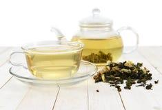 Pote y taza de cristal del té con el platillo aislado Imagen de archivo