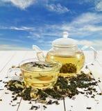 Pote y taza de cristal del té en fondo del cielo Foto de archivo libre de regalías