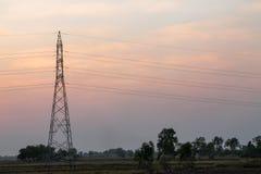Poteau à haute tension, tour à haute tension avec le fond de coucher du soleil de ciel photos stock
