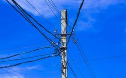 Poteau électrique à haute tension contre le ciel bleu et les nuages et le soleil lumineux Photo stock