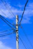 Poteau électrique à haute tension contre le ciel bleu et les nuages et le soleil lumineux Images stock