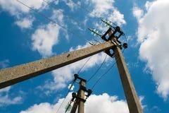 Poteau électrique avec des fils contre un ciel bleu avec des nuages Photo libre de droits
