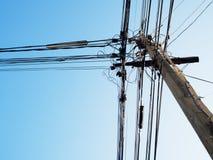 Poteau électrique et câbles électriques embrouillés avec le ciel bleu Images libres de droits