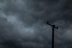 Poteau électrique et ciel foncé Photographie stock