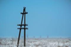 Poteau électrique solitaire sur le fond d'un paysage d'hiver Photos libres de droits