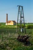 Poteau d'énergie électrique et vieux bâtiment de pompe de vapeur Photographie stock libre de droits