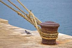 Poteau d'amarrage rouillé d'amarrage avec des cordes de bateau Images stock
