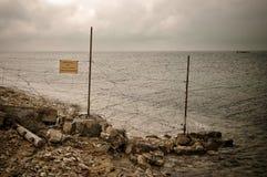 Poteau de frontière de sécurité avec le barbelé sur la côte Photos stock