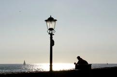 Poteau de lampe et homme de repos Photographie stock