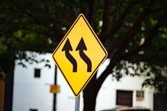 Poteau de signalisation jaune avec les flèches noires onduleuses image libre de droits