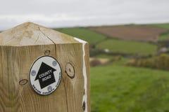 Poteau en bois avec le signe de Devon County Road et les champs verts au-delà Image stock