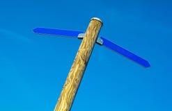Poteau en bois avec les flèches bleues de direction Images libres de droits