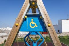 Poteau en bois d'oscillation avec le signe handicapé et simbol dans le terrain de jeu Image stock